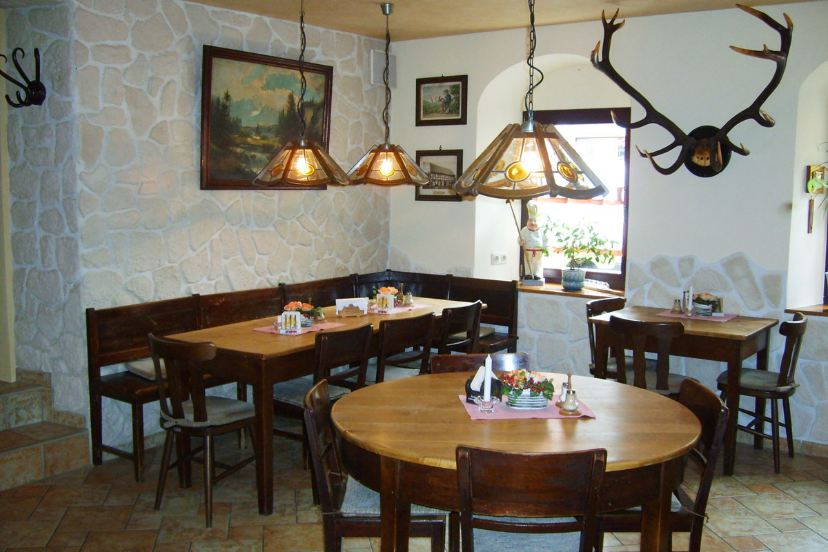 Gaststube mit Tischen, Stühlen und Lampen
