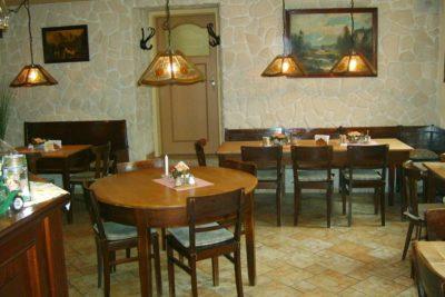 Gaststube mit Tischen, Bildern und Lampen